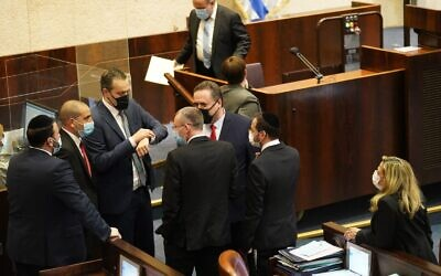 Coalition MKs watch the final moments of the 23rd Knesset tick away in the Knesset plenum on December 23, 2020. (Knesset spokesperson)