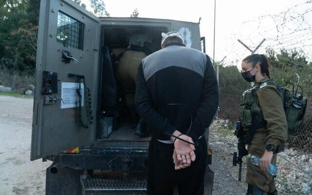 A photo released by the Israel Defense Forces on December 24, 2020, shows soldiers in the West Bank detaining a suspect in the suspected murder of Israeli woman Esther Horgen. (Israel Defense Forces)