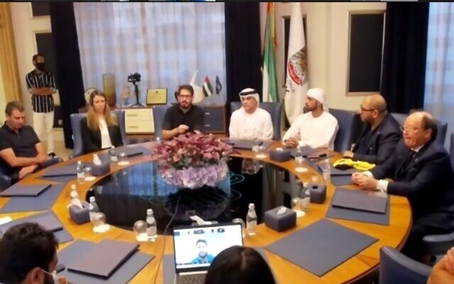 Beitar Jerusalem owner Moshe Hogeg (center, black t-shirt), his new partner Sheikh Hamad bin Khalifa Al Nahyan (fourth from right), and the sheikh's son Mohammad, Beitar's new vice-chairman (third from right), discuss their new joint ownership of the Israeli soccer club at an online press conference from the UAE, December 8, 2020. At far-right is Solly Wolf, president of the UAE Jewish community. (Screenshot)