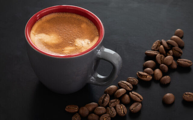 Illustrative image of a cup of coffee against the background of roasted coffee beans (Lenti Hill; iStock by Getty Images)