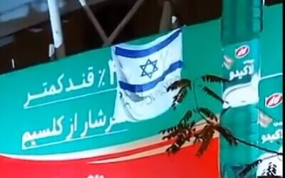 An Israeli flag and sign reading 'Thank you, Mossad' in a Tehran suburb (screencapture via Twitter)