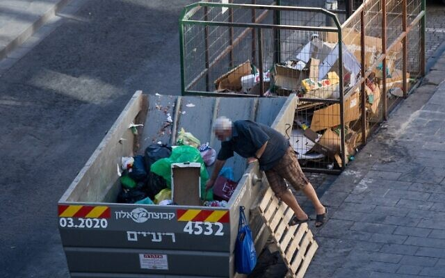 A man searches in a garbage container in downtown Jerusalem, August 17, 2020. (Yonatan Sindel/Flash90)