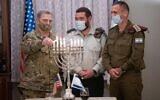 US Chairman of the Joint Chiefs of Staff Gen. Mark Milley lights a menorah on the eighth night of the Hannukah holiday alongside Cpt. Josh Gerstein and IDF Chief of Staff Aviv Kohavi in army headquarters in Tel Aviv on December 17, 2020. (Israel Defense Forces)