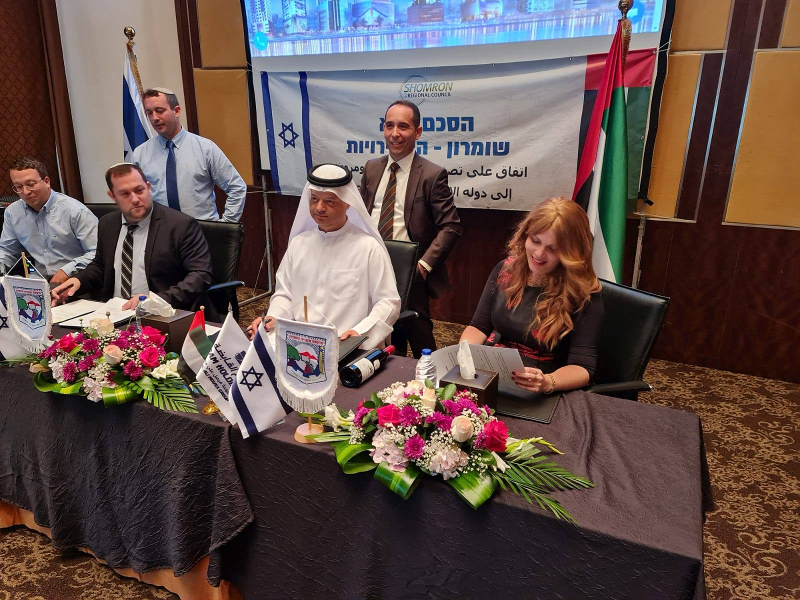 Tura Winery co-owner Vered Ben Sa'adon, right, and Samaria Regional Council head Yossi Dagan, second from left, attend a signing ceremony for a business deal in Dubai, December 7, 2020 (courtesy Tura Winery)