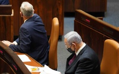 Blue and White leader Benny Gantz (left) is seen with his back to Prime Minister Benjamin Netanyahu as the Knesset approves a preliminary reading of a bill to dissolve parliament, December 2, 2020 (Danny Shem-Tov / Knesset spokesperson's office)