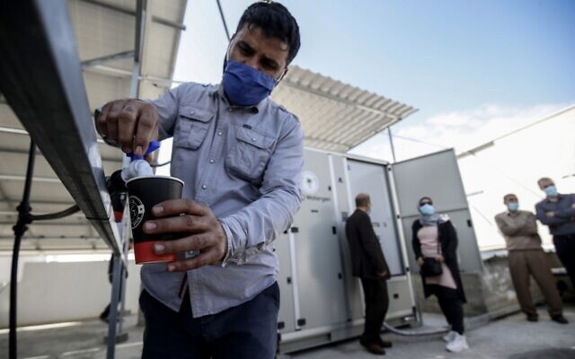A Palestinian man fills a cup of water from a solar-powered water generator that extracts potable water straight from the air donated by Watergen, a company owned by a Russian-Israeli businessman, in the town of Khan Yunis in the southern Gaza Strip, on November 16, 2020 (SAID KHATIB / AFP)