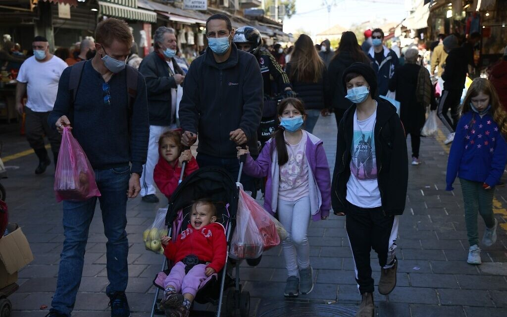 A family walks in the Mahane Yehuda market in Jerusalem on December 27, 2020. (MENAHEM KAHANA/AFP)