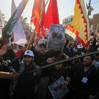 Iraqi supporters of the Hashed al-Shaabi paramilitary carry portraits of  Iraqi commander Abu Mahdi al-Muhandis and Iranian Revolutionary Guards commander Qasem Soleimani during a demonstration in Baghdad's western Shoala neighborhood on January 1, 2021, demanding the expulsion of US forces from Iraq and calling for revenge for the killing of al-Muhandis and Soleimani, ahead of the January 3 anniversary of the US drone strike (AHMAD AL-RUBAYE / AFP)