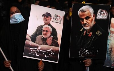 People carry portraits of late Iraqi commander Abu Mahdi al-Muhandis and Iranian commander Qasem Soleimani at Baghdad Airport, in Baghdad on January 2, 2021, at the site of their killing (AHMAD AL-RUBAYE / AFP)