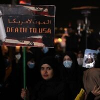 An Iraqi woman carries a poster at Baghdad Airport, in Baghdad on January 2, 2021, at the site of the killing of an Iraqi commander and the commander of the Iranian Revolutionary Guard (AHMAD AL-RUBAYE / AFP)