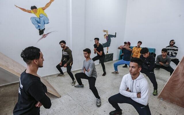 A coach trains Palestinian children at the Wallrunners Parkour Academy's training facility in Gaza City on December 28, 2020. (MAHMUD HAMS / AFP)
