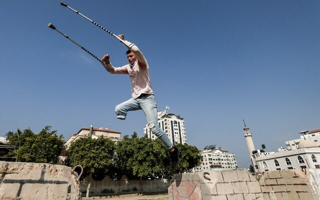 Mohamed Aliwa, a Palestinian youth whose leg was amputated near the knee in 2018 after he was injured during clashes with the   Israeli army in violent protests along the border with Israel, shows off his parkour skills despite his disability and while on crutches in Gaza City on January 4, 2021. (MAHMUD HAMS / AFP)
