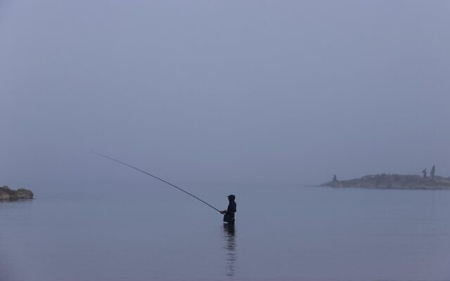 A man goes fishing amid morning fog in the coastal city of Netanya on January 6, 2021. (JACK GUEZ / AFP)