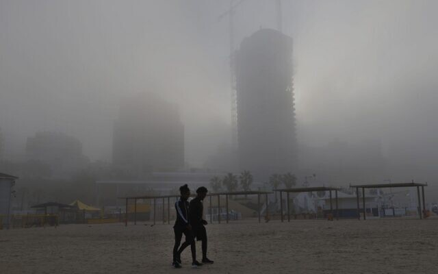 Two pedestrians walk on the beach early on January 6, 2021, in the coastal city of Netanya amid the morning fog on the first week of the new year. (JACK GUEZ / AFP)