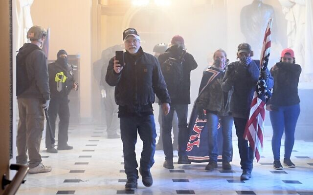 Supporters of US President Donald Trump enter the Capitol as tear gas fills the corridor on January 6, 2021, in Washington. (Saul Loeb/AFP)