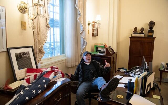 Richard Barnett, a supporter of US President Donald Trump, sits inside the office of US Speaker of the House Nancy Pelosi inside the US Capitol in Washington, DC, January 6, 2021. (Saul Loeb/AFP)