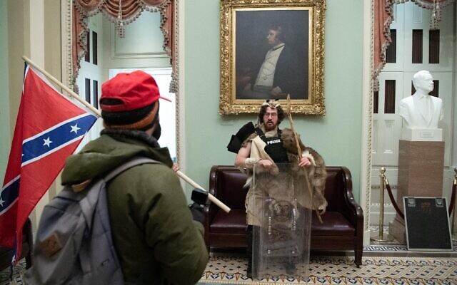 Aaron Mostofsky (in fur pelt) and a protester with the Confederate flag in the US Capitol Rotunda on January 6, 2021, in Washington, DC. (Saul Loeb/AFP)
