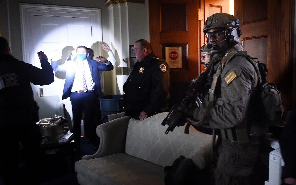Congress staffers hold up their hands while Capitol Police Swat teams check everyone in the room as they secure the floor of Trump suporters in Washington, DC on January 6, 2021.  (Olivier DOULIERY / AFP)