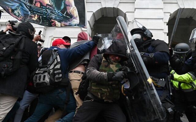In this file photo taken on January 6, 2021, riot police push back a crowd of supporters of US President Donald Trump after they stormed the Capitol building in Washington, DC. (Photo by ROBERTO SCHMIDT / AFP)