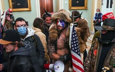 Supporters of US President Donald Trump, including Jake Angeli (aka Jacob Chansley), a QAnon supporter, enter the Capitol in Washington, DC, on January 6, 2021. (Saul Loeb/AFP)