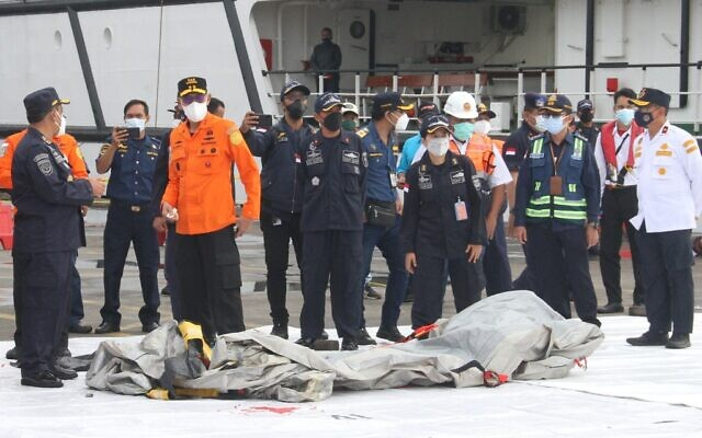 Rescue workers inspect recovered debris at the port in Jakarta on January 10, 2021, during the search operation for Sriwijaya Air flight SJY182 which crashed after takeoff from Jakarta on January 9. (Dany Krisnadhi / AFP)