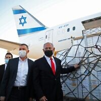 Israel's Prime Minister Benjamin Netanyahu (R) and Health Minister Yuli Edelstein (C) attend a ceremony for the arrival of a plane carrying a shipment of Pfizer-BioNTech anti-coronavirus vaccine, at Ben Gurion airport near the Israeli city of Tel Aviv on January 10, 2021. (Motti MILLROD / POOL / AFP)