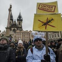 A demonstrator dressed in a costume of prisoner holds a banner reading the word 'Untermensch' (sub-human) referring to a Nazi term attends the protest against COVID-19 government measures on January 10, 2021, in the old Town Square in Prague. (Michal Cizek / AFP)