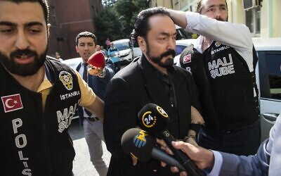In this file photo taken on July 11, 2018, Turkish police officers escort Adnan Oktar (C) in Istanbul, as he is arrested on fraud charges (DOGAN NEWS AGENCY / AFP)