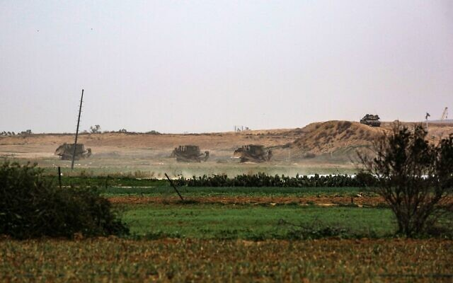 Israeli military bulldozers are pictured clearing the buffer zone on Israel's border with Gaza, opposite the Palestinian city of Khan Yunis in the southern Gaza Strip, on January 13, 2021.  (Said Khatib/AFP)