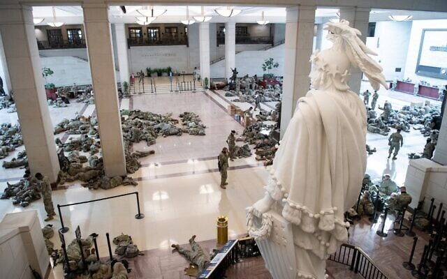 Members of the National Guard rest in the Capitol Visitors Center on Capitol Hill in Washington, DC, January 13, 2021, ahead of an expected House vote impeaching US President Donald Trump.  (SAUL LOEB / AFP)