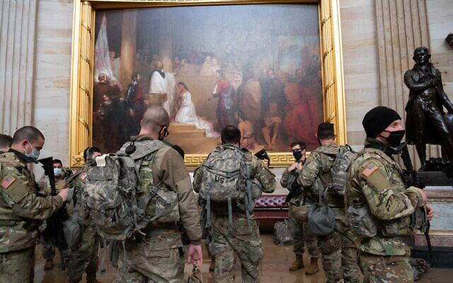 Members of the National Guard walk through the Rotunda of the US Capitol in Washington, DC, January 13, 2021, ahead of an expected House vote impeaching US President Donald Trump.  (SAUL LOEB / AFP)