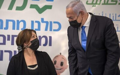 Prime Minister Benjamin Netanyahu speaks to an unidentified woman during his visit to a coronavirus vaccination facility in the northern Israeli Arab city of Nazareth, on January 13, 2021. (Gil ELIYAHU / POOL / AFP)
