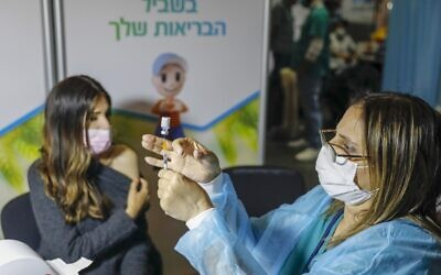A Israeli healthcare worker prepares a dose of the COVID-19 vaccine at a Clalit health clinic in Jerusalem, on January 14, 2021 (AHMAD GHARABLI/AFP)