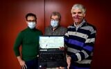 OrphAnalytics CEO Claude Alain Roten (C) poses with staff members and a laptop using the text analysis software on January 6, 2021 (Fabrice COFFRINI / AFP)