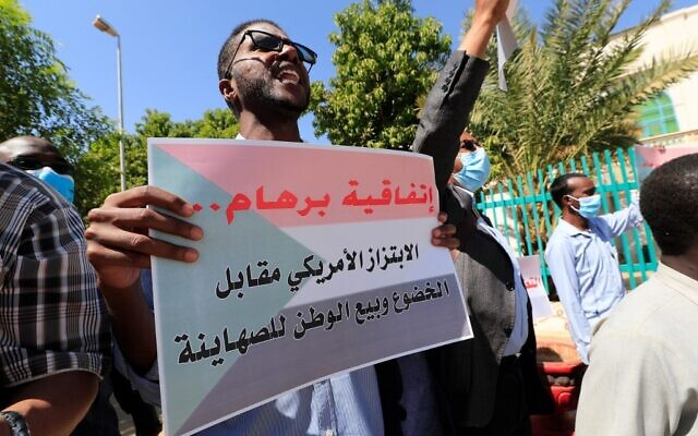 A Sudanese demonstrator holds a placard that reads in Arabic 'The Abraham Accords, a US provocation and the sale of our homeland to the Zionists' during a rally against their country's recent signing of a deal on normalizing relations with Israel, outside the cabinet offices in the capital Khartoum, on January 17, 2021 (ASHRAF SHAZLY / AFP)