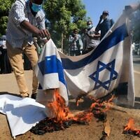 Sudanese demonstrators burn Israeli flags during a rally against their country's recent signing of a deal on normalizing relations with the Jewish state, outside the cabinet offices in the capital Khartoum, on January 17, 2021 (ASHRAF SHAZLY / AFP)
