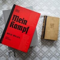 The Polish academic edition of Adolf Hitler's 'Mein Kampf' (L) is seen next to an original edition of the book from 1942 (R) on the table of Eugeniusz Cezary Król, author of the translation and historical commentary of the academic edition, in his flat in Warsaw, on January 15, 2021. (Photo by Wojtek RADWANSKI / AFP)
