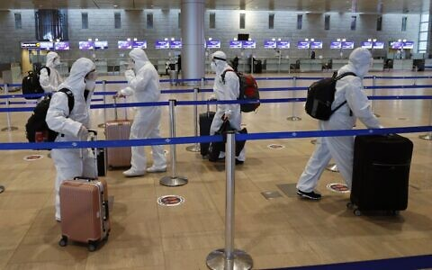 Passengers wearing full protective suits and masks to protect against the COVID-19 pandemic push their luggage trolleys at the departures area at Ben Gurion Airport on January 19, 2021. (Jack Guez/AFP)