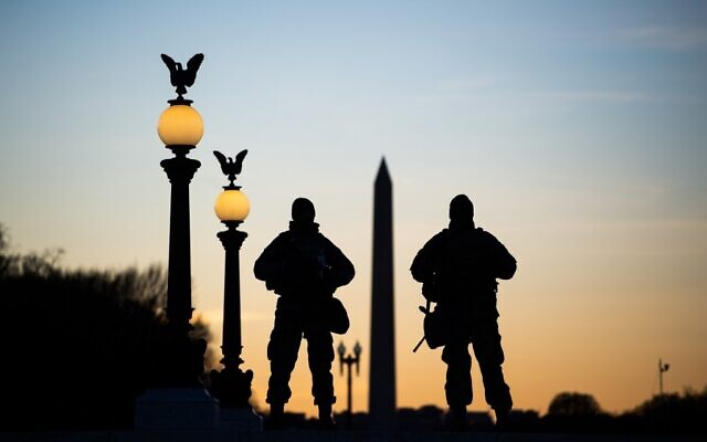 US National Guard soldiers are seen in silhouette as they keep guard in front of the Capitol Building and near the Washington Monument in Washington, DC on January 19, 2021, ahead of the 59th inaugural ceremony for President-elect Joe Biden and Vice President-elect Kamala Harris. (Photo by ROBERTO SCHMIDT / AFP)