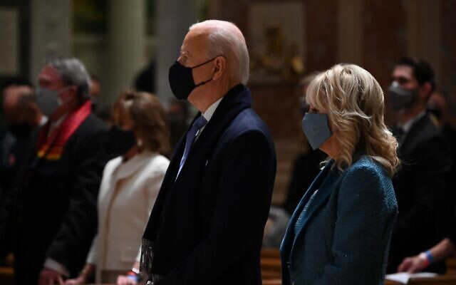US President-elect Joe Biden (C) and incoming First Lady Jill Biden attend Mass at the Cathedral of St. Matthew the Apostle in Washington, DC, on January 20, 2021. (Photo by JIM WATSON / AFP)