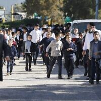 Children of the ultra-Orthodox Jewish community walk outside a  school, which was open in violation of COVID-19 lockdown rules, following its closure by security forces, in the city of Ashdod on January 22, 2021 (JACK GUEZ / AFP)