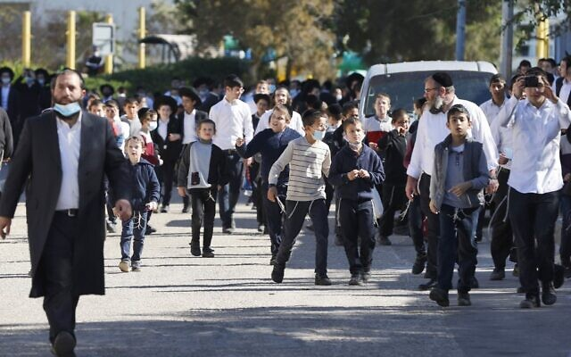 Haredi schoolchildren outside a  school that opened in violation of COVID-19 lockdown rules following its closure by security forces, in the city of Ashdod on January 22, 2021. (Jack Guez/AFP)