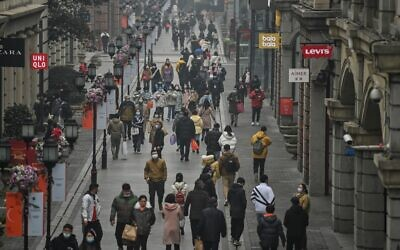 People walk along a pedestrian street in Wuhan, China's central Hubei province on January 23, 2021, one year after the city went into lockdown to curb the spread of the coronavirus. (Hector Retamal/AFP)