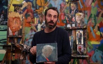 Israeli painter Iddo Markus speaks during an interview at his studio, surrounded by his paintings of former US president Donald Trump, in the northern port city of Haifa, on January 22, 2021 (Emmanuel DUNAND / AFP)