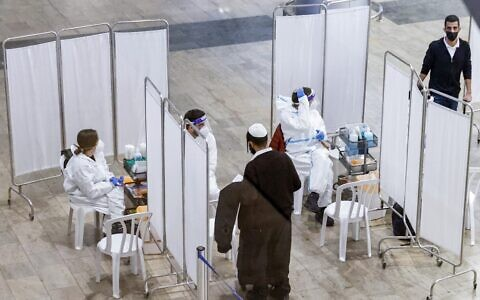 A traveler approaches a medic to be sampled while testing for the COVID-19 coronavirus disease, upon arrival at the rapid testing center in Ben-Gurion International Airport, near Tel Aviv, on January 24, 2021.  (JACK GUEZ / AFP)