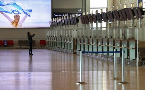 A woman takes a photo at the deserted departure hall at Israel's Ben-Gurion International Airport in Lod, near Tel Aviv, on January 25, 2021. (Emmanuel DUNAND / AFP)