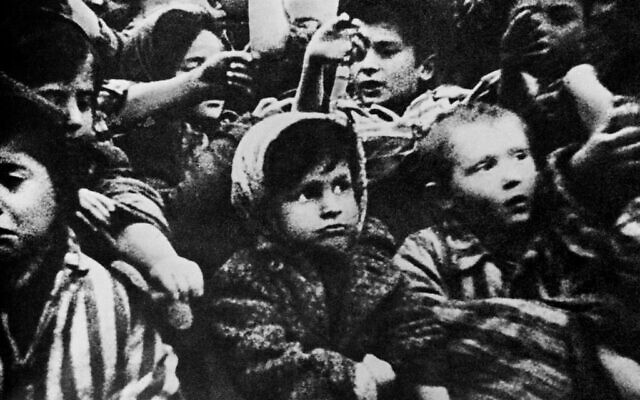 Surviving children of the Auschwitz concentration camp show their tattoos in January 1945, January 15, 1945. (Screen capture: 'Auschwitz' by Soviet film director Elizaveta Svilova via AFP)