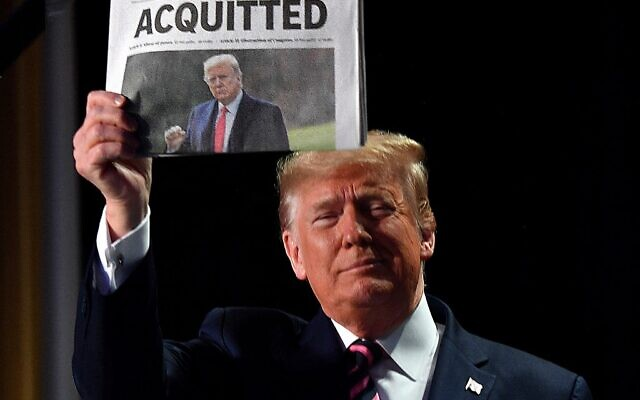 """In this file photo taken on February 06, 2020, US President Donald Trump holds up a newspaper that displays a headline """"Acquitted,"""" as he arrives to speak at the 68th annual National Prayer Breakfast in Washington, DC (Nicholas Kamm / AFP)"""