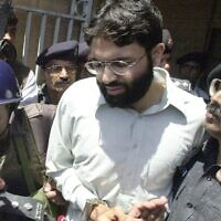 In this March 29, 2002, photo, Ahmed Omar Saeed Sheikh, the alleged mastermind behind Wall Street Journal reporter Daniel Pearl's kidnap-slaying, is escorted by police in Karachi, Pakistan. (Aamir Qureshi/AFP)