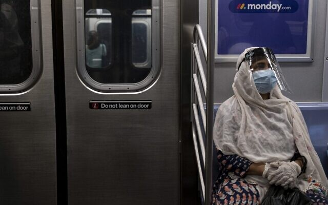 In this file photo taken on July 16, 2020, a woman wearing a face mask and shield sits in a subway train during rush hour amid the coronavirus pandemic in New York City (Johannes EISELE / AFP)